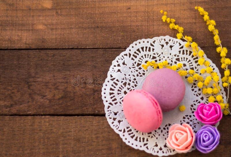 Två makron på servett med blommor på träbakgrund arkivfoton
