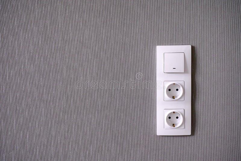 Två makthåligheter och ljus strömbrytare på den gråa väggen fotografering för bildbyråer