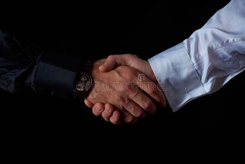 Två manliga affärsmän i svartvita skjortaskakahänder, svart bakgrund, studioskytte fotografering för bildbyråer