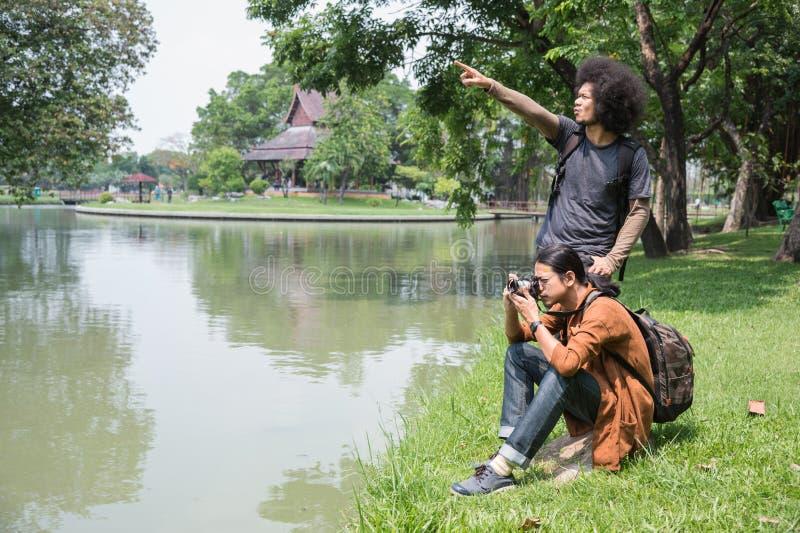 Två manliga asiatiska handelsresande kopplar av, genom att sitta på grönt gräs nära dammet, parkerar offentligt, handelsresanden  fotografering för bildbyråer