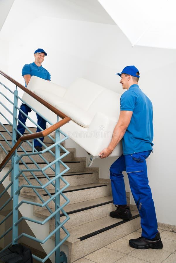 Två manliga flyttkarlar som bär Sofa On Staircase royaltyfri fotografi