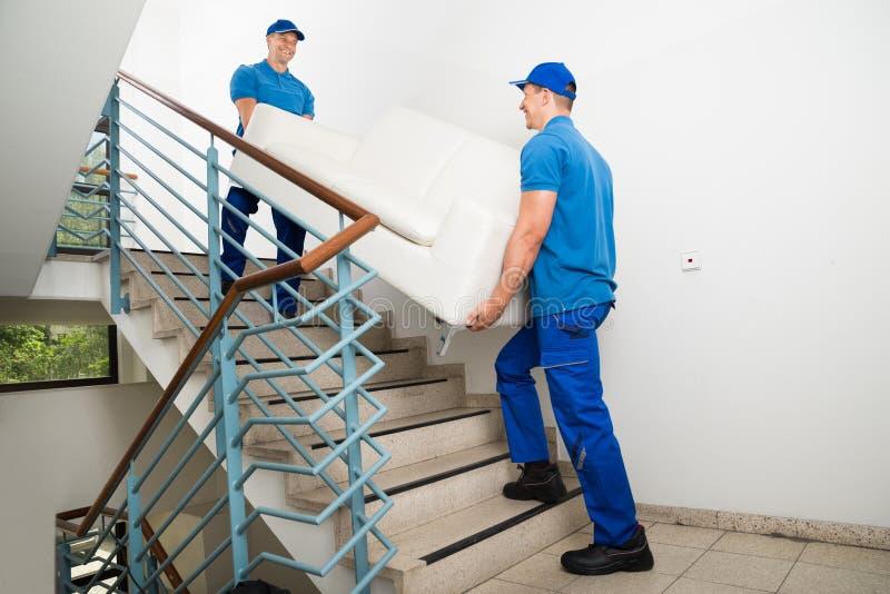 Två manliga flyttkarlar som bär Sofa On Staircase fotografering för bildbyråer