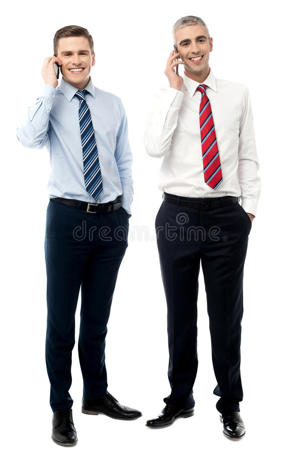 Två manliga ledare som talar på mobiltelefonen royaltyfri foto