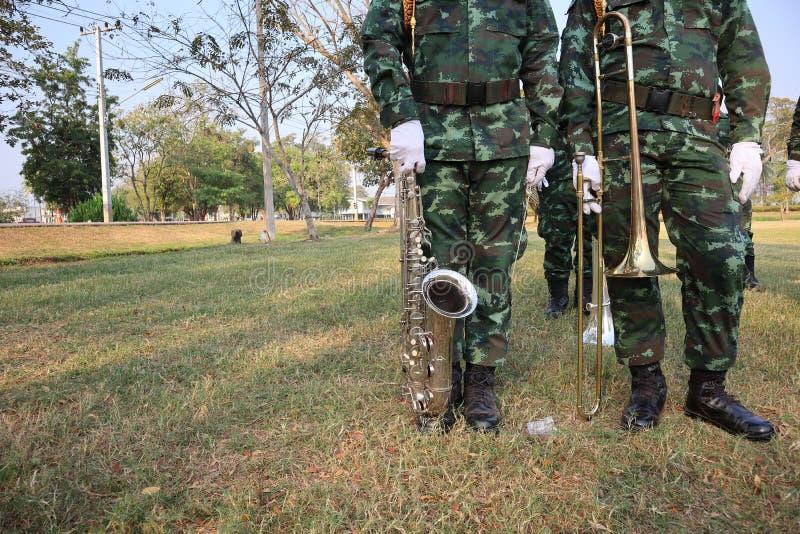 Två manliga soldater står rymma en bakgrund för instrumentsaxofon- och trombongräsmatta royaltyfri fotografi