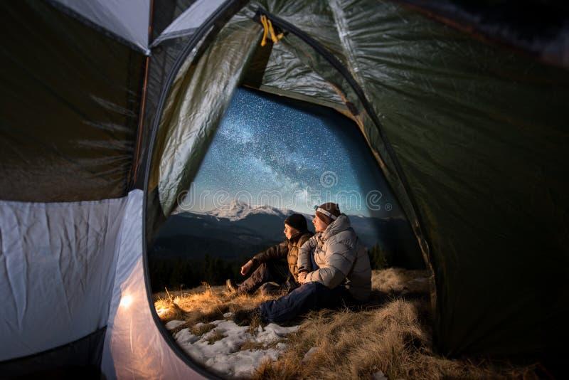 Två manliga turister har en vila i campa i bergen på natten under natthimmel mycket av stjärnor och den mjölkaktiga vägen arkivfoto