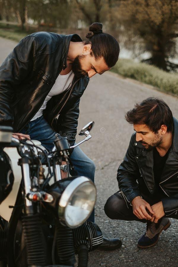 Två manliga vänner som allvarligt ser på motorcykeln på vägen arkivfoto