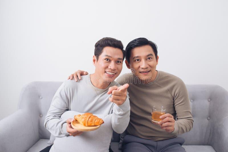 Två manliga vänner som hemma håller ögonen på fotbollsammanträde på soffan royaltyfri foto