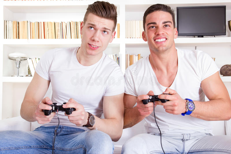 Två manliga vänner som spelar videospelet med kontrollanter arkivfoto