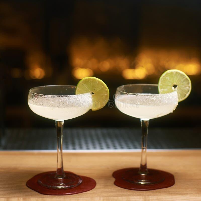 Två margaritacoctailar med tequila och Cointreau på trästångräknaren som dekoreras med limefruktskivor och att salta fotografering för bildbyråer