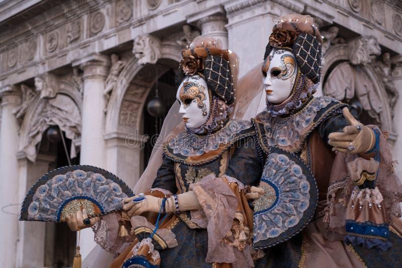 Två maskeringar i dräkt, med dekorerade fans som står av bågarna på St-fläckar, kvadrerar framme under den Venedig karnevalet royaltyfri foto