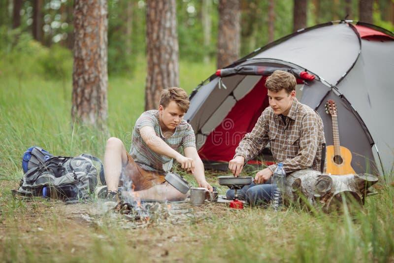 Två med- campare som gör te och förbereder mat vid ett tält royaltyfria bilder