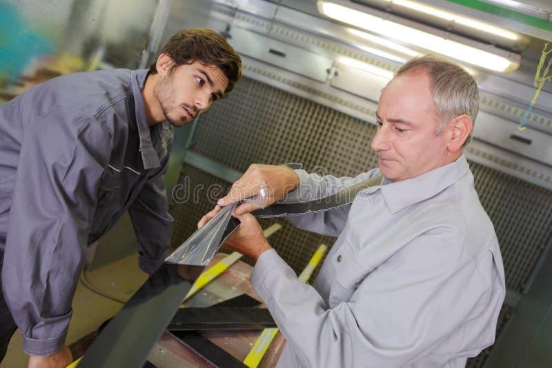 Två mekaniker som arbetar i seminarium royaltyfria bilder