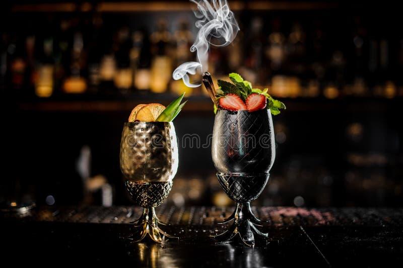 Två metallexponeringsglas av nya sommarcoctailar som dekoreras med frukt på stången, kontrar royaltyfri bild