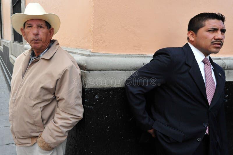Två mexicanska män, en pensionär och en vuxen människa som är stående tillbaka att dra tillbaka arkivbilder