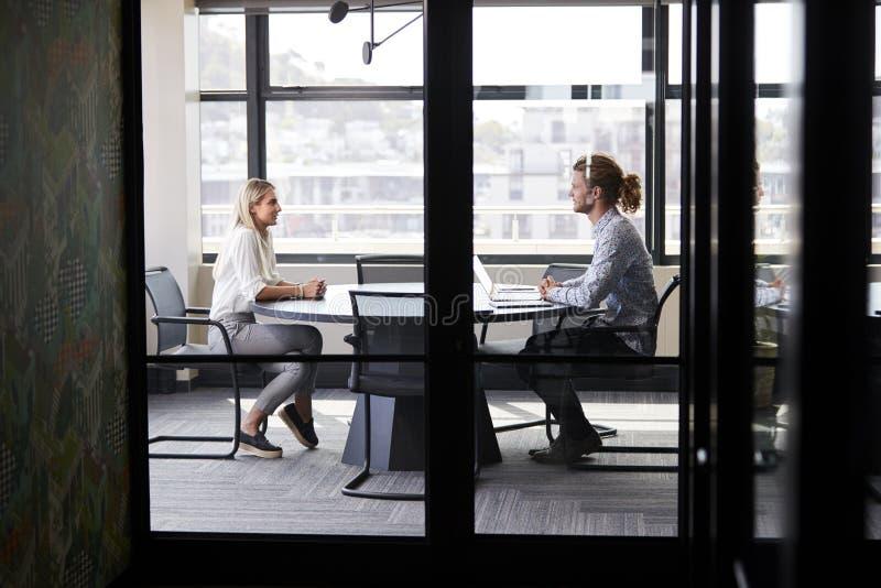 Två millennial affärscreatives i en mötesrum för en jobbintervju, sedd igenom glasvägg royaltyfria bilder