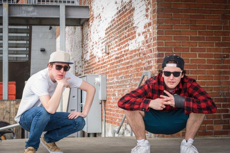 Två millennialsmän som poserar vid tegelstenväggen i stad royaltyfria bilder