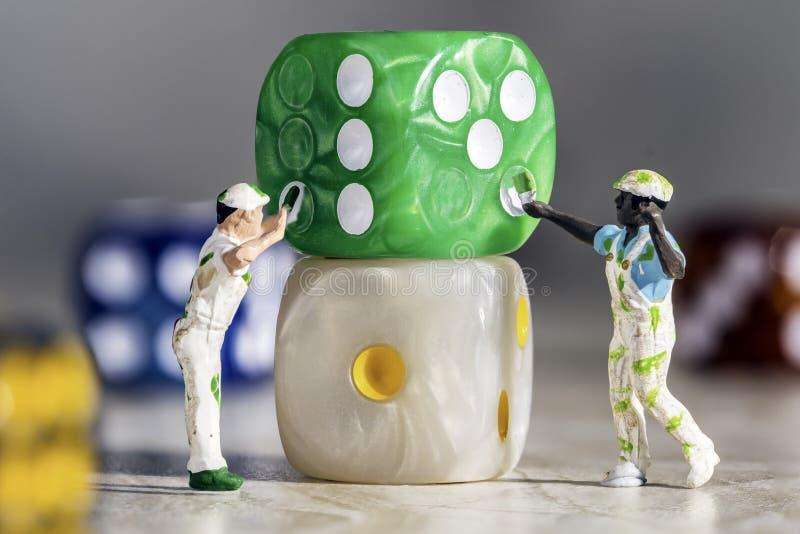 Två miniatyrfolkmålare som målar grön tärning med vita kärnor på en Grey Marble Background arkivbild