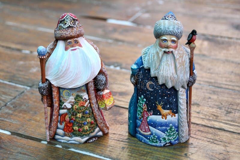 Två miniatyrSantas som snidas från trä - ryss Handcrafts arkivfoto