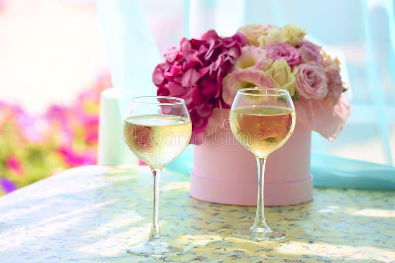 Två misted exponeringsglas av kall champagne i den delikata buketten för bakgrund av blommor royaltyfria bilder
