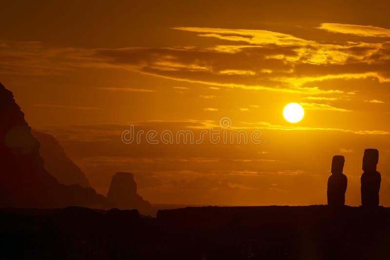 Två moais mot orange soluppgång arkivbilder