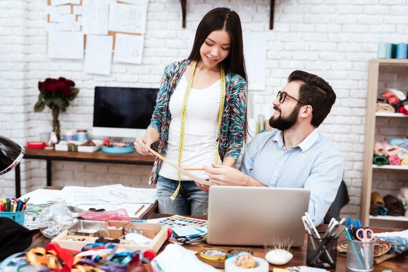 Två modeformgivare som diskuterar modellteckningen royaltyfria bilder