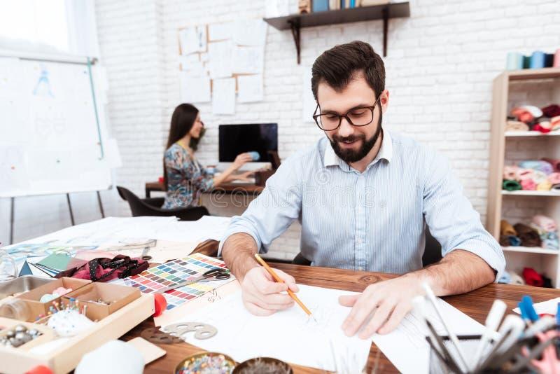 Två modeformgivare som drar på papper fotografering för bildbyråer