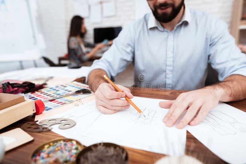 Två modeformgivare som drar på papper arkivfoto