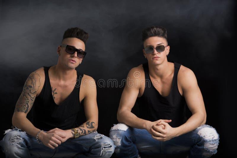 Två moderiktiga manliga vänner för höft i studioskott arkivfoto
