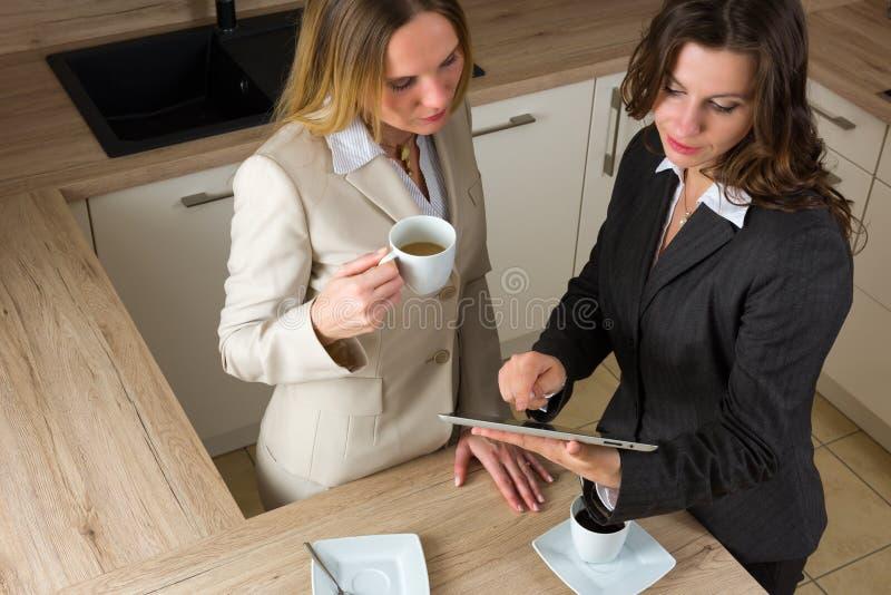Två moderna affärskvinnor med minnestavlan och kaffe i köket royaltyfria foton