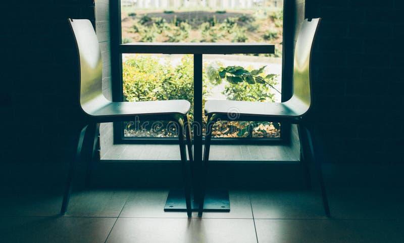 Två moderna stilstolar nära den gulliga lilla tabellen nära fönstret med skottet för inre för tegelstenvägg det svartvita fotografering för bildbyråer