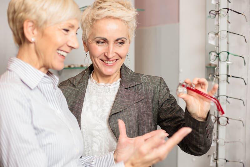 Två mogna kvinnor som shoppar för modeller för exponeringsglas för recept för välja och för försöka olika, arkivbild