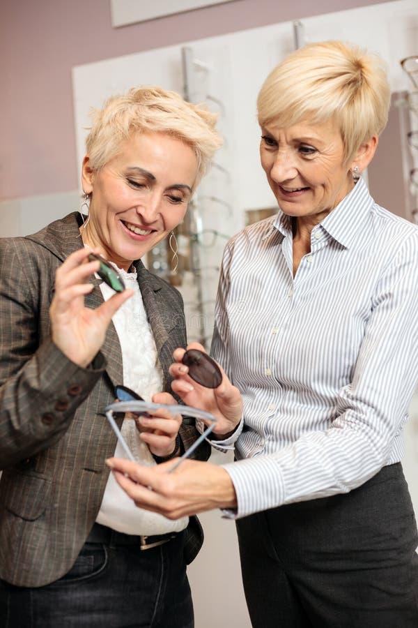 Två mogna kvinnor som väljer receptlinser för att matcha med nya läs- exponeringsglas royaltyfri fotografi