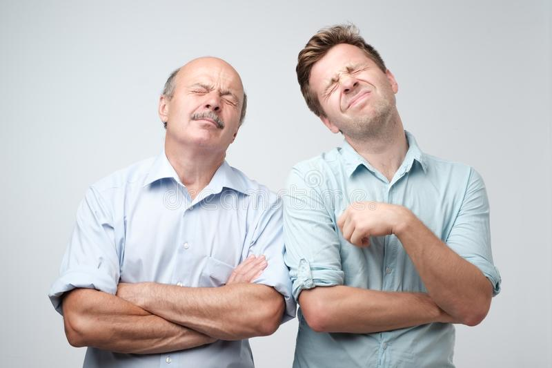 Två mogna män fader och son med borrat matat upp uttryckt, blickar misshog upp royaltyfria foton