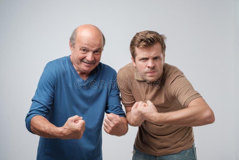 Två mogna starka män som lyfter grep hårt om nävar som visar deras makt royaltyfri foto