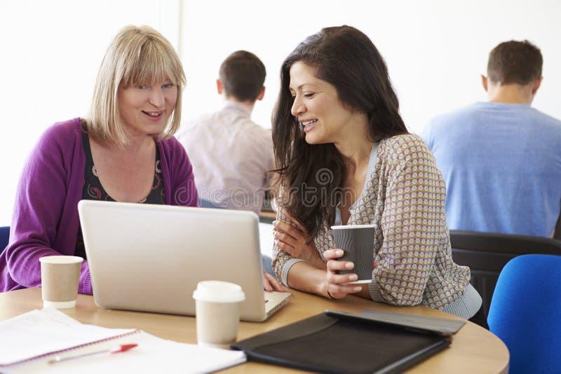 Två mogna studenter för kvinnlig som arbetar tillsammans genom att använda bärbara datorn arkivfoto