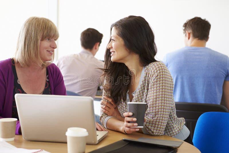 Två mogna studenter för kvinnlig som arbetar tillsammans genom att använda bärbara datorn arkivbild