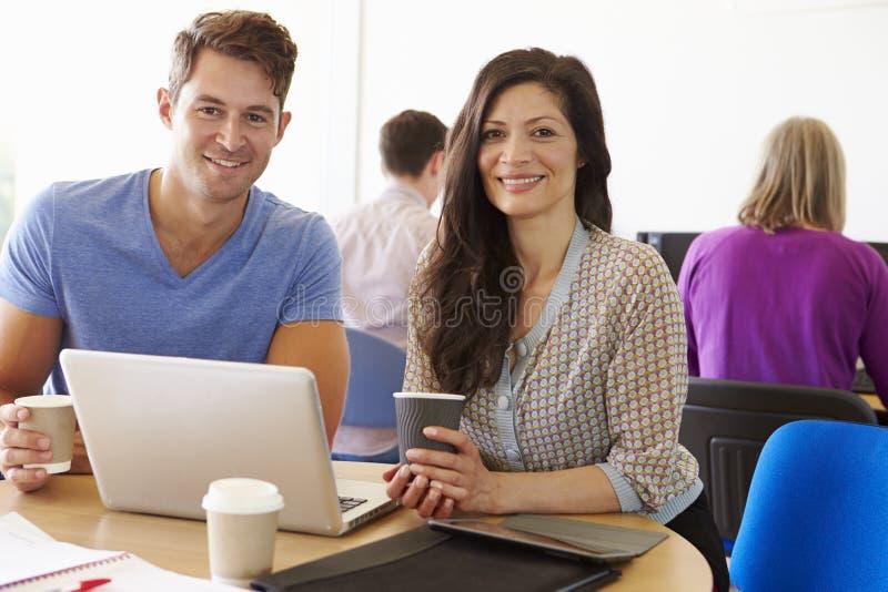 Två mogna studenter som arbetar tillsammans genom att använda bärbara datorn arkivfoto