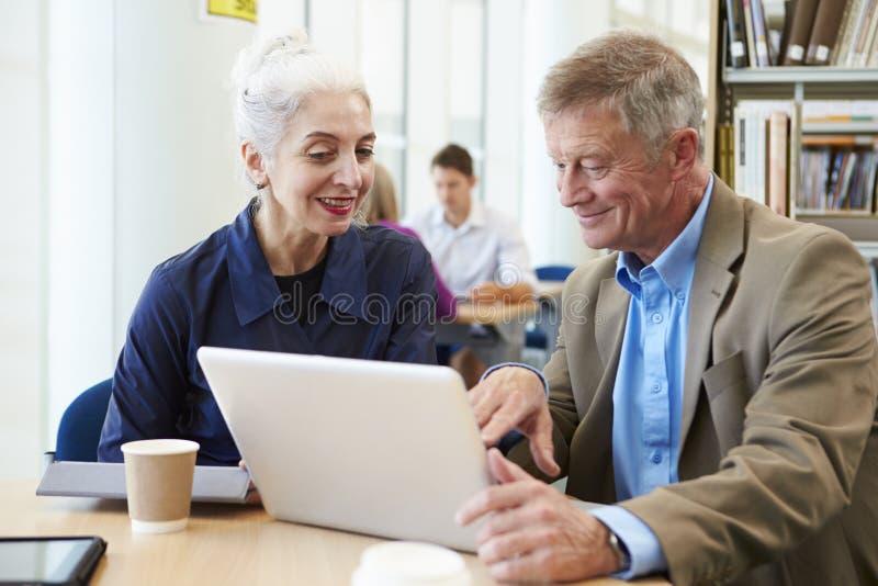 Två mogna studenter som tillsammans arbetar i arkiv genom att använda bärbara datorn arkivfoton