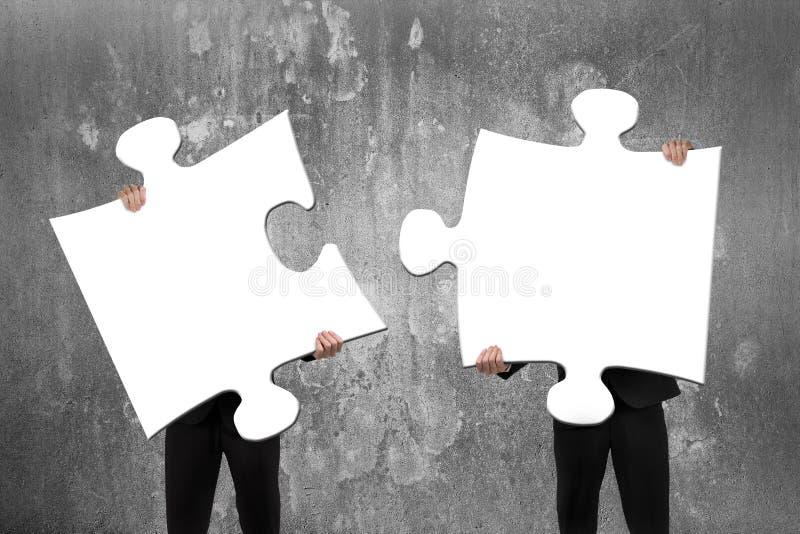 Två monterande vita pussel för affärsfolk med concret royaltyfri foto