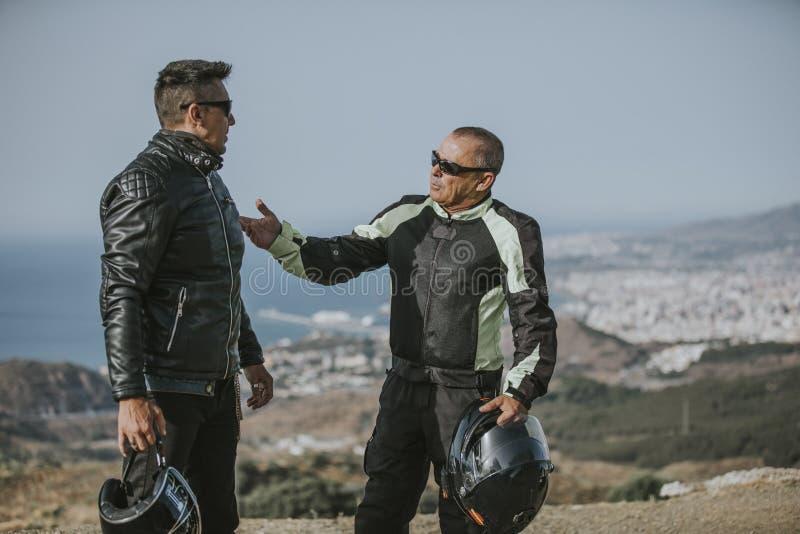 Två mopedryttare som talar under en motorcykelritt, bryter, med havet och den blåa himlen i bakgrunden arkivfoto