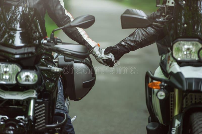 Två motorcyklister rymmer händer, medan sitta på motorcyklar royaltyfria foton