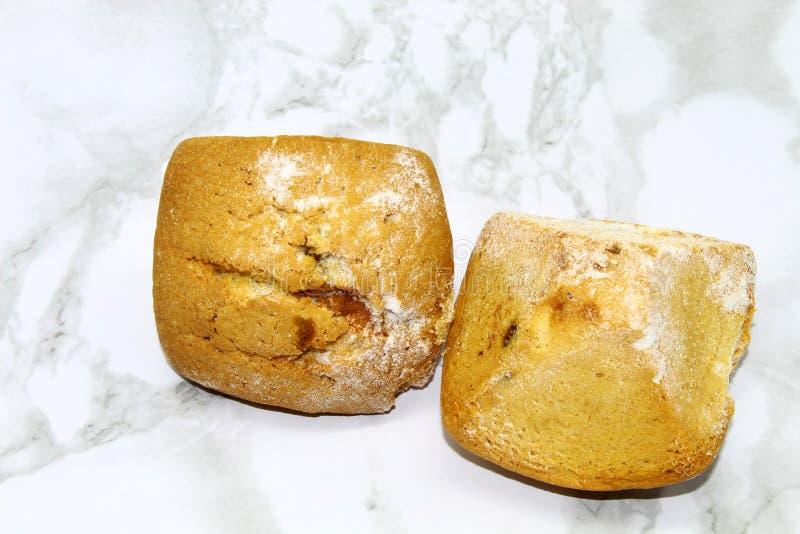 Två muffin med russin på en mönstrad bakgrund royaltyfri fotografi