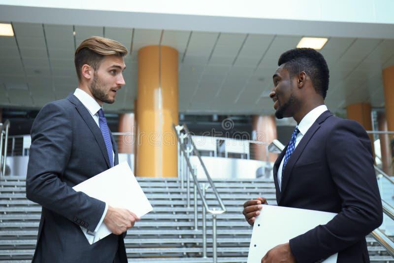 Två multinationella unga affärsmän som talar medan trappa i modern kontorsbyggnad arkivfoton
