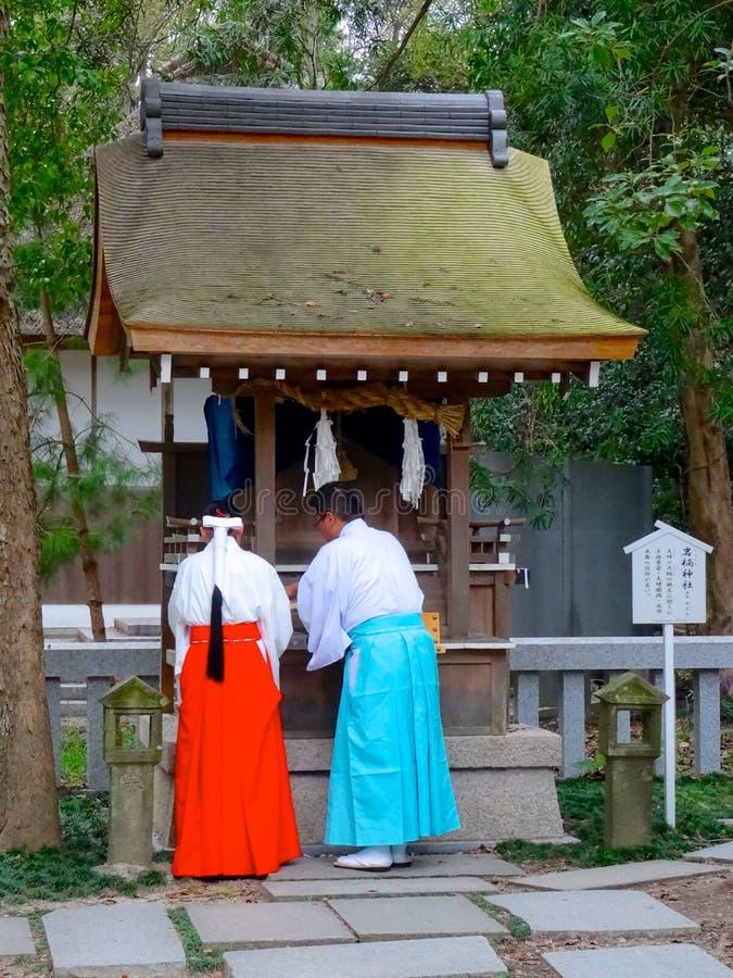 Två munkar som framme står av en Sessha på den Izanagi relikskrin royaltyfria foton
