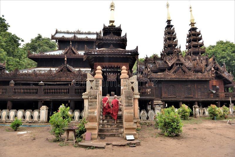 Två munkbuddistungar med röda traditionella dräkter som upp klättrar tempeltrappan royaltyfri foto