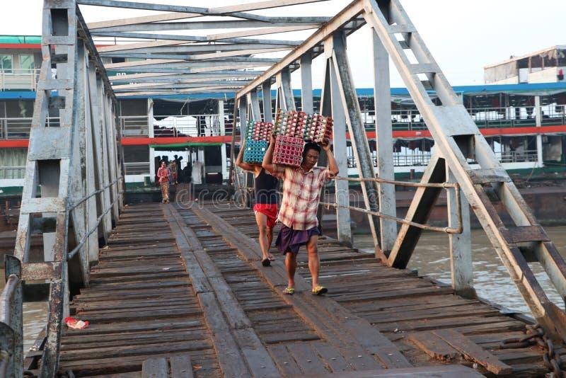 Två Myanmese arbetare bär andägg i en spjällåda landsätter från skeppet och går förbi bron av hamnen på den Yangon floden royaltyfri bild