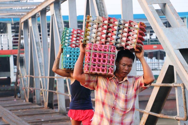 Två Myanmese arbetare bär andägg i en spjällåda landsätter från skeppet och går förbi bron av hamnen på den Yangon floden fotografering för bildbyråer