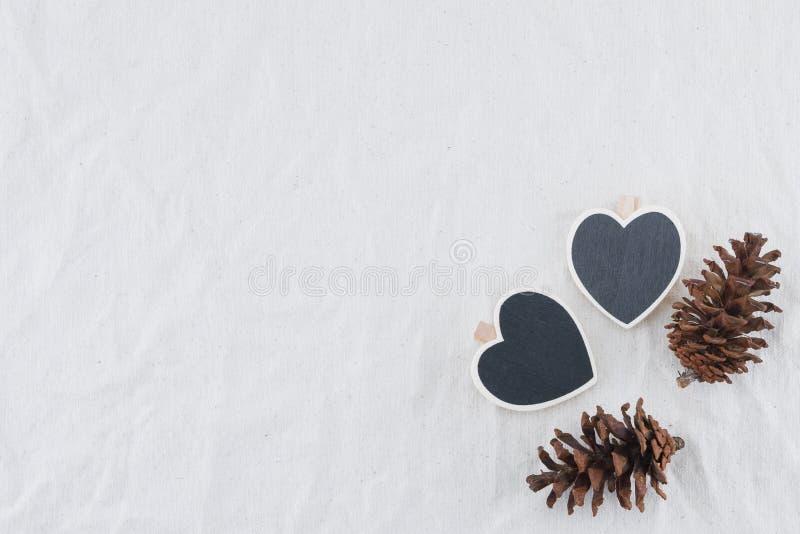 Två mycket lilla hjärtaformsvart tavla med pinecones arkivbild