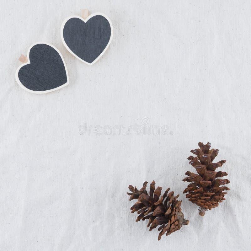 Två mycket lilla hjärtaformsvart tavla med pinecones royaltyfri foto