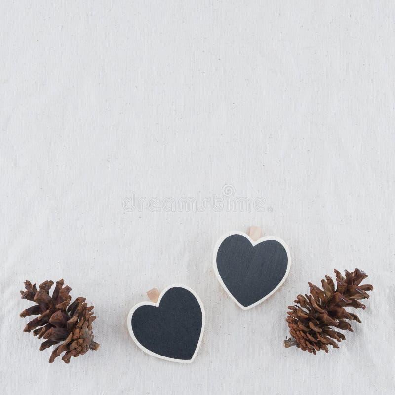 Två mycket lilla hjärtaformsvart tavla med pinecones royaltyfri fotografi